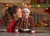 Portrait of mother and baby in christmas decorated kitchen