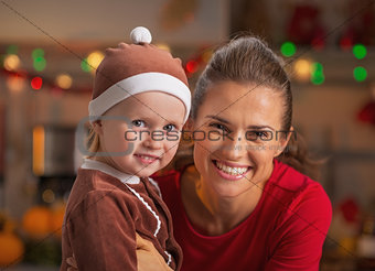 Portrait of smiling mother and baby in christmas decorated kitch