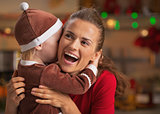 Baby embracing happy mother and in christmas decorated kitchen