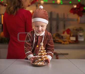 Baby helping mother making christmas preparations on kitchen