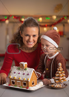 Portrait of happy mother and baby making christmas cookie house