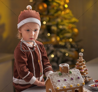 Portrait of baby with christmas cookie house