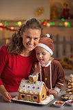 Portrait of smiling mother and baby with christmas cookie house