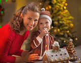 Portrait of happy mother and baby eating cookie in christmas dec