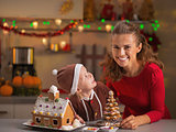 Smiling mother and baby with christmas cookie house in kitchen