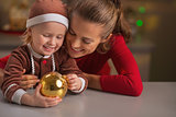 Portrait of happy mother and baby with christmas ball
