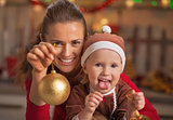 Happy mother and baby showing christmas ball