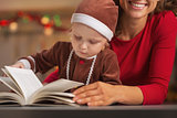 Mother and baby in christmas costume reading book