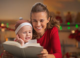 Happy mother and baby reading book in christmas decorated kitche