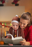 Happy mother and baby in christmas costume reading book