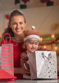Portrait of happy mother and baby checking christmas shopping ba