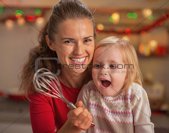 Portrait of happy mother and surprised baby looking on whisk