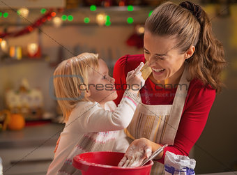 Baby trying to smear mothers nose with flour while making christ