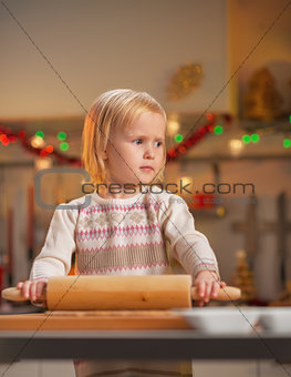 Portrait of baby rolling pin dough in christmas decorated kitche