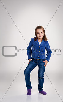little girl in blue jeans and jacket posing in the studio
