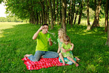young family blowing bubbles on nature
