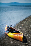 Orange and Yellow Kayak With Oars on the Sea Shore