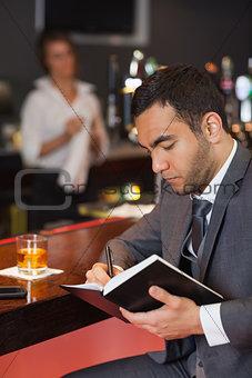 Cheerful businessman writing on his datebook