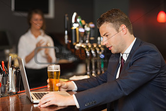 Businessman having a beer while working on his laptop