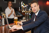 Businessman having a pint while working on his laptop