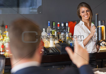 Handsome man ordering a drink from gorgeous waitress