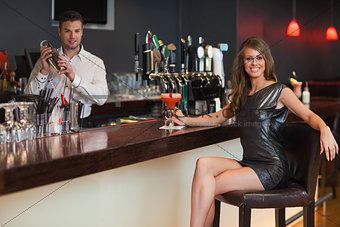 Gorgeous woman in black dress having a cocktail