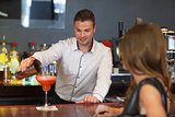 Handsome bartender serving cocktail to gorgeous woman