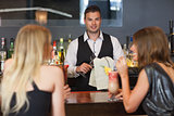 Handsome bartender working while gorgeous women talking