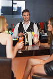 Handsome bartender working while gorgeous friends talking