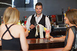 Handsome bartender working while gorgeous friends speaking