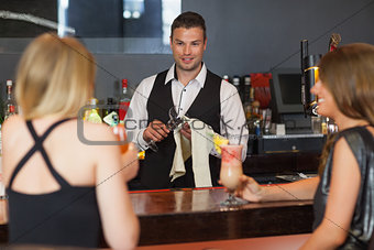 Handsome bartender working while gorgeous friends speaking