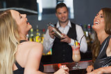 Handsome bartender working while gorgeous friends laughing