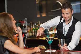 Handsome bartender serving cocktail to attractive woman