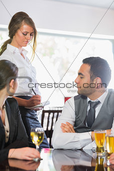 Business people ordering a dinner from waitress
