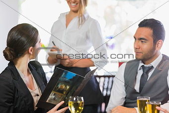 Businesswoman ordering dinner from smiling waitress