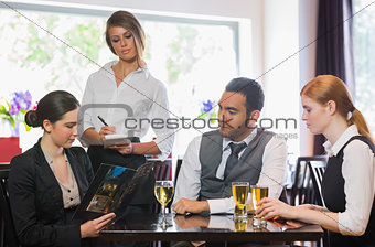 Three business people ordering dinner from waitress