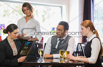Three business people ordering a dinner in restaurant
