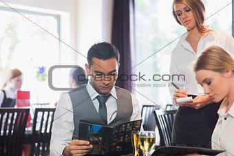 Handsome businessman reading the menu