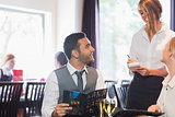 Handsome businessman ordering food from waitress