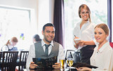 Business people and waitress smiling at camera