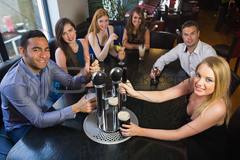 Young friends sitting together and pulling pints in a restaurant
