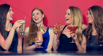 Attractive friends clubbing holding cocktails