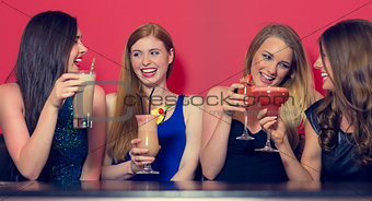 Four friends having a party holding cocktails