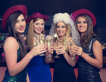 Attractive friends clinking champagne glasses at hen night