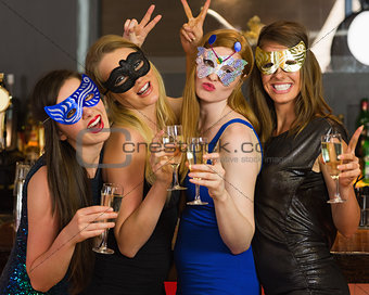 Attractive women wearing masks holding champagne