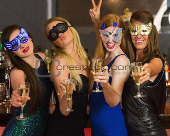 Happy friends wearing masks showing champagne glasses