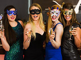 Laughing friends wearing masks holding champagne glasses
