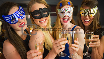 Smiling friends holding champagne glasses wearing masks
