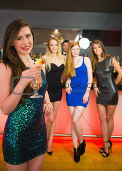 Smiling woman standing in front of of her friends holding cocktail