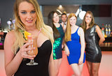 Blonde attractive woman holding cocktail standing in front of her friends